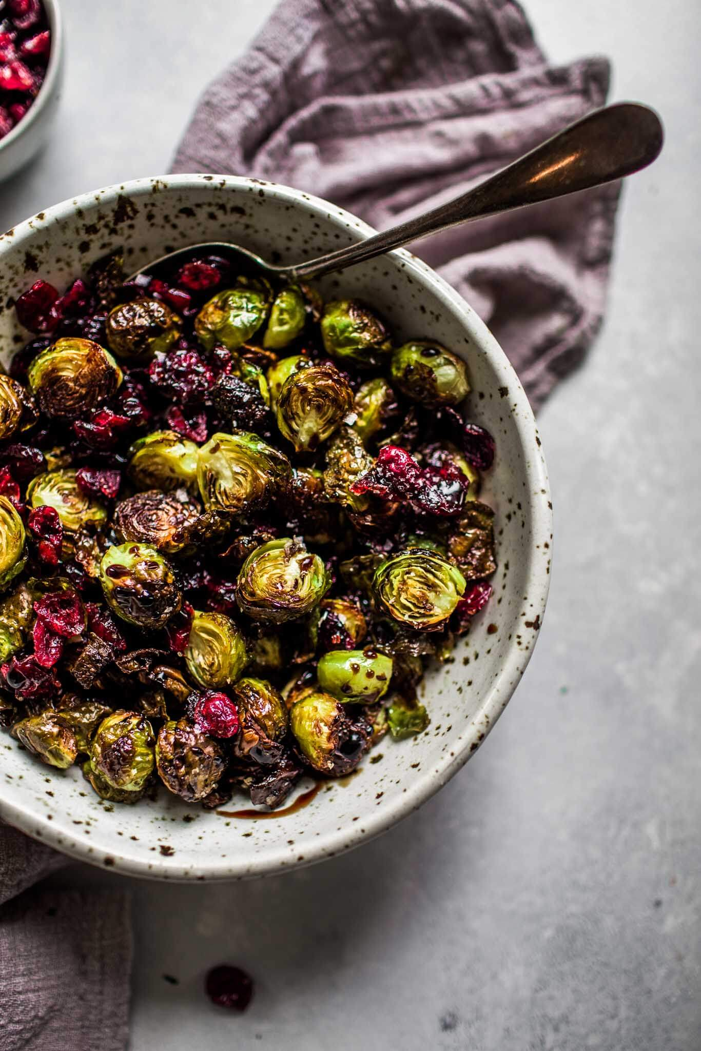 Bowl of roasted brussels sprouts with balsamic reduction & cranberries.