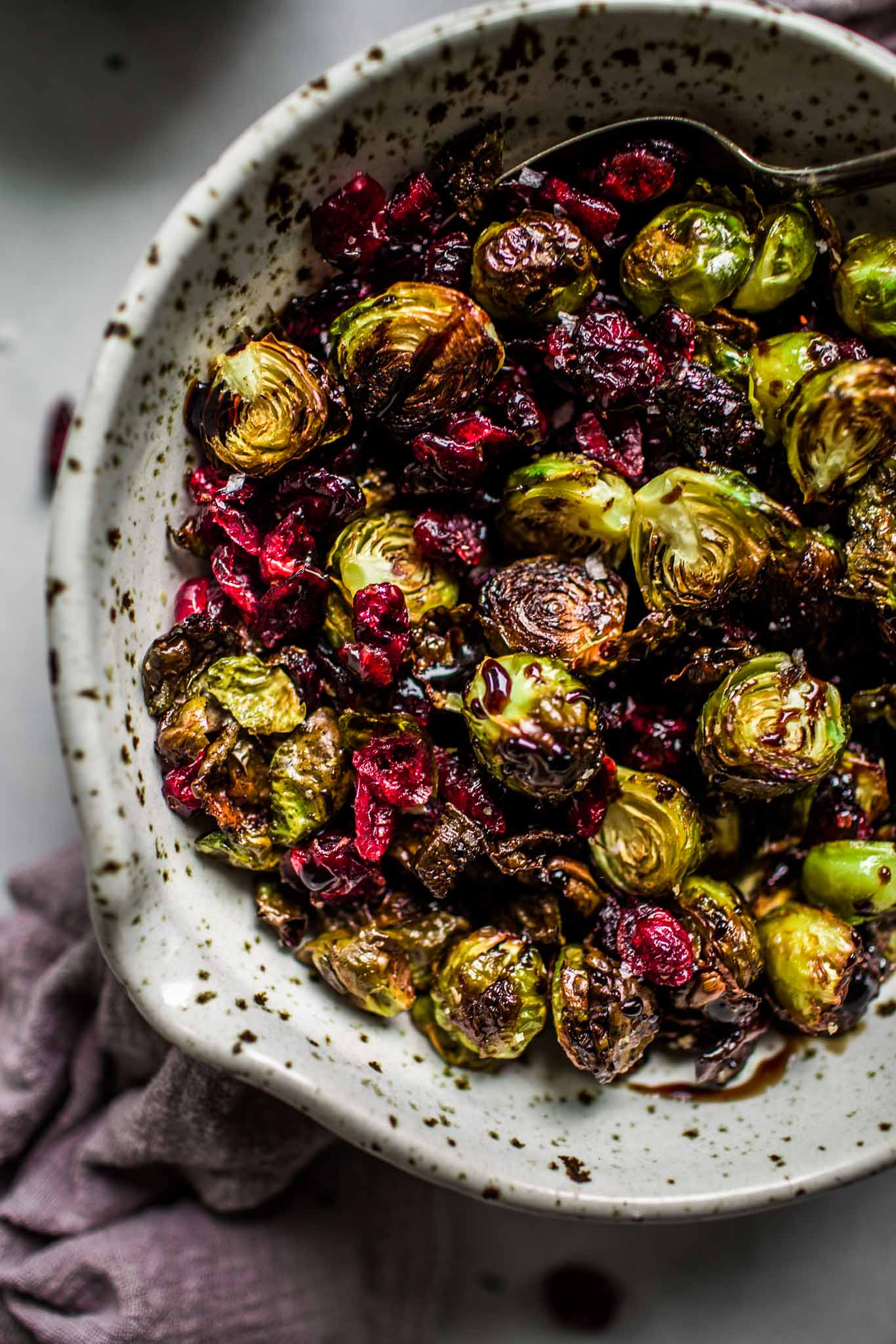 Overhead close up of bowl of roasted brussels sprouts with balsamic reduction & cranberries.