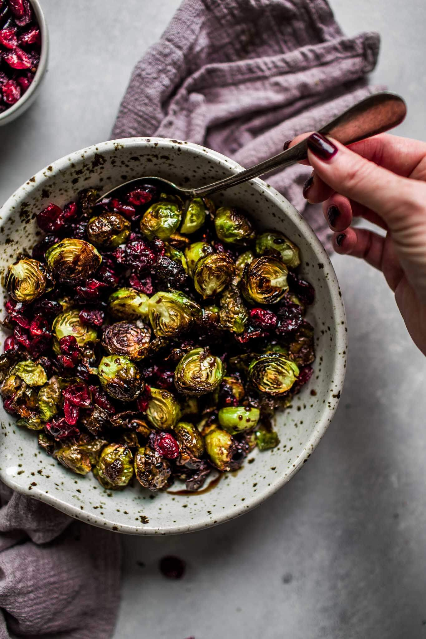 Hand reaching for bowl of roasted brussels sprouts with balsamic reduction & cranberries.