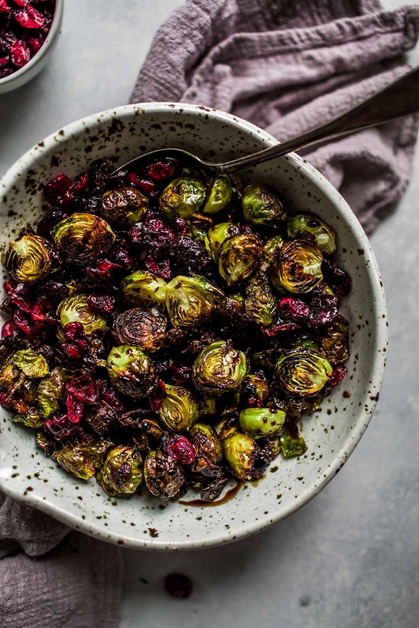 Overhead shot of bowl of roasted brussels sprouts with balsamic reduction & cranberries.