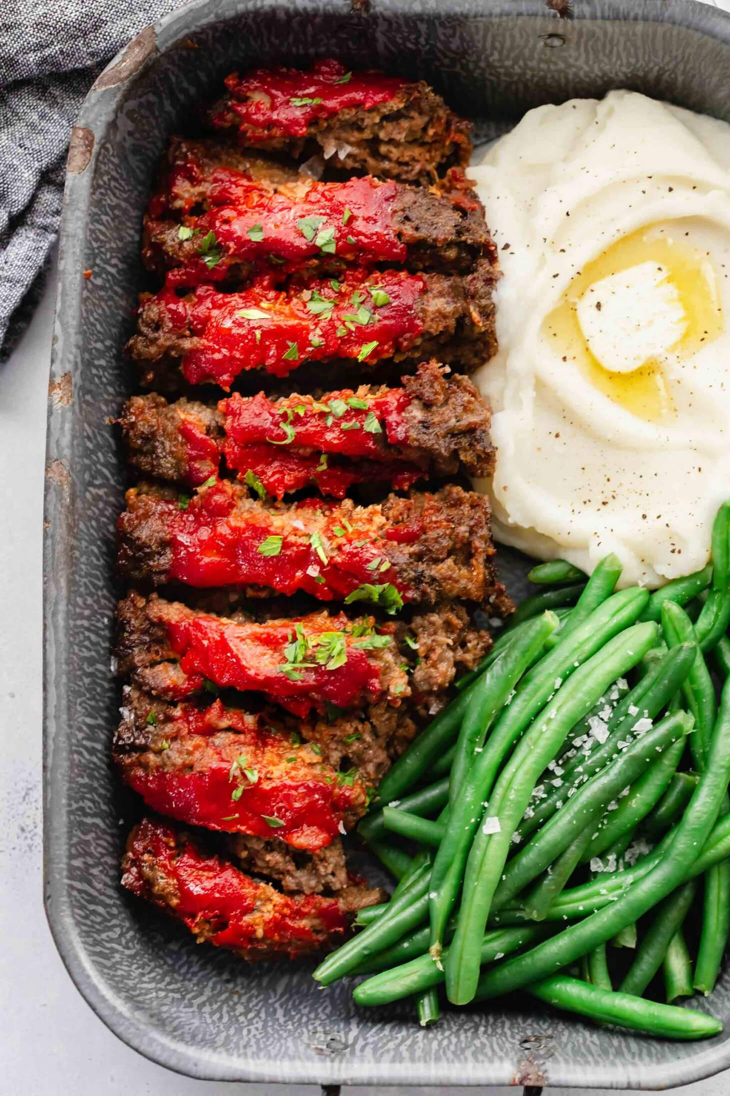 Sliced BOSTON MARKET meatloaf in serving tray with green beans and mashed potatoes.