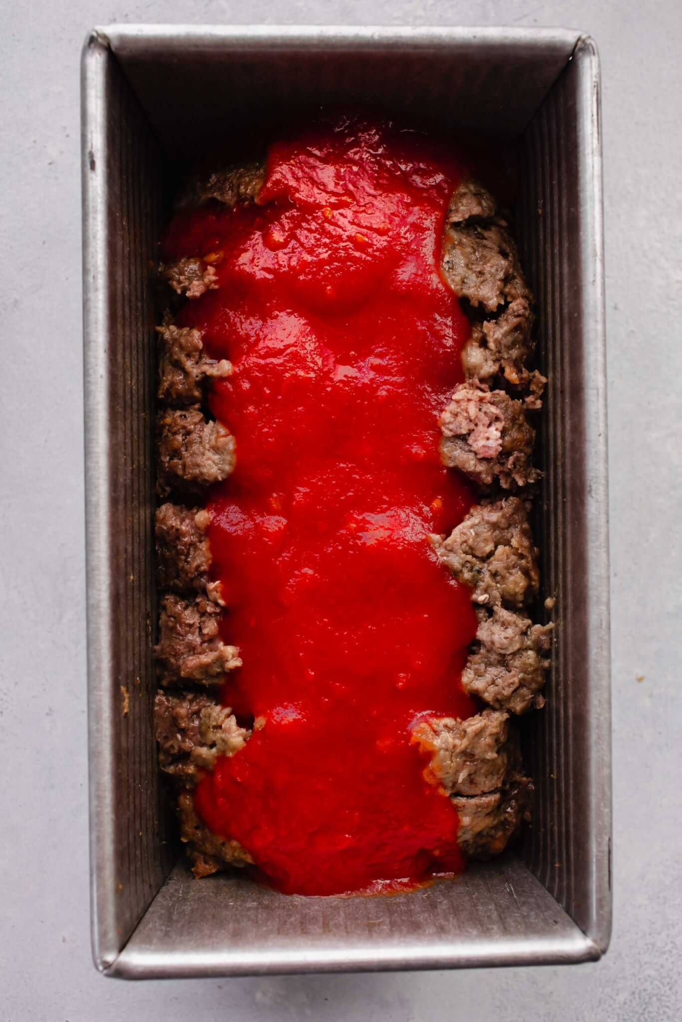 Half baked meatloaf after slicing and drizzling on tomato sauce.