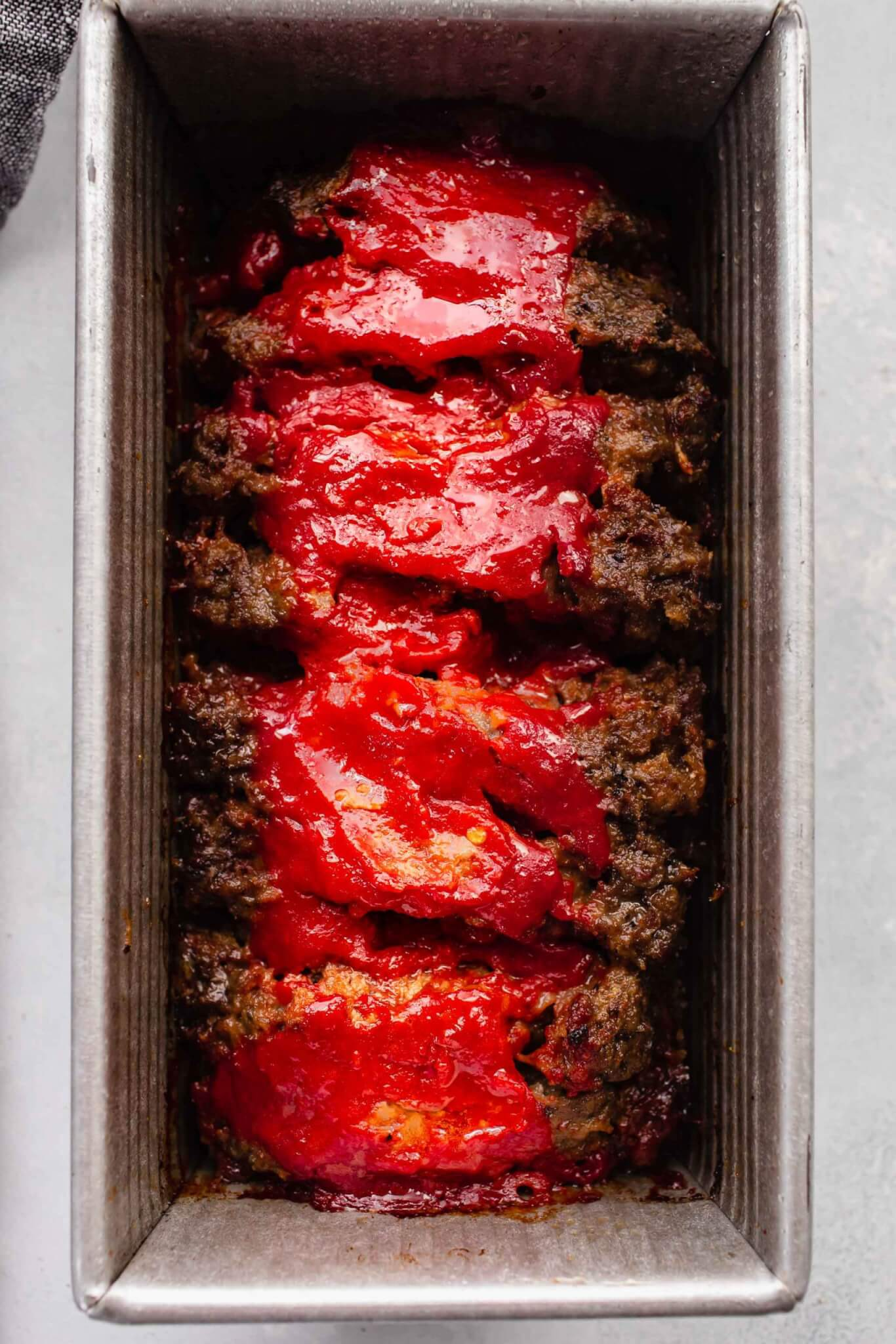 Finished baked meatloaf in loaf pan.