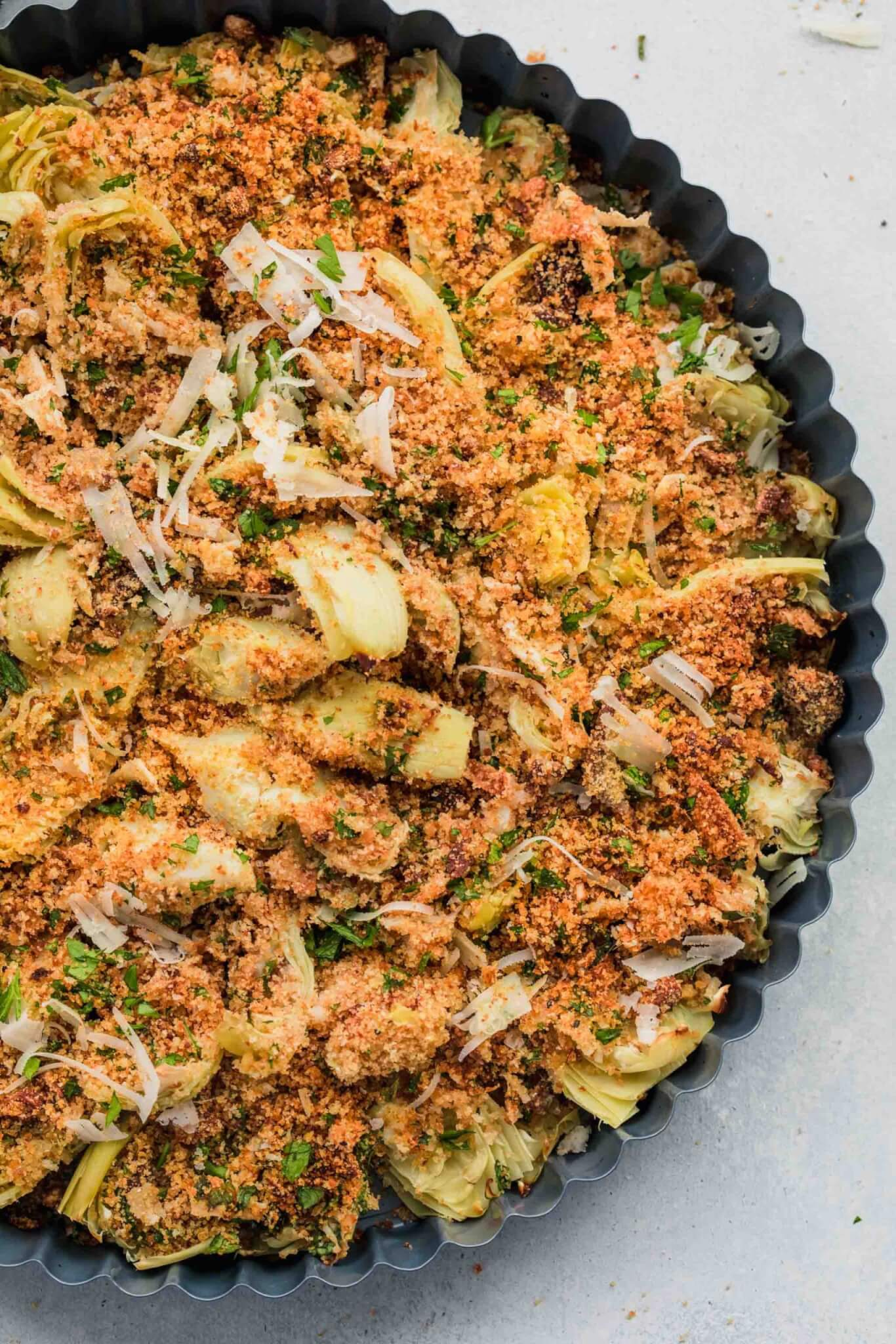 Baked artichoke hearts in baking dish after cooking.