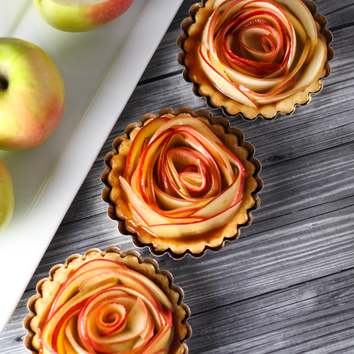 These Salted Caramel Apple Tartlets are not only amazingly delicious, but beautiful too! Thin apple slices are arranged to look like a rose and drizzled with a yummy, spiked salted caramel sauce. Perfect for Valentine's Day or holiday dinners. | platingsandpairings.com