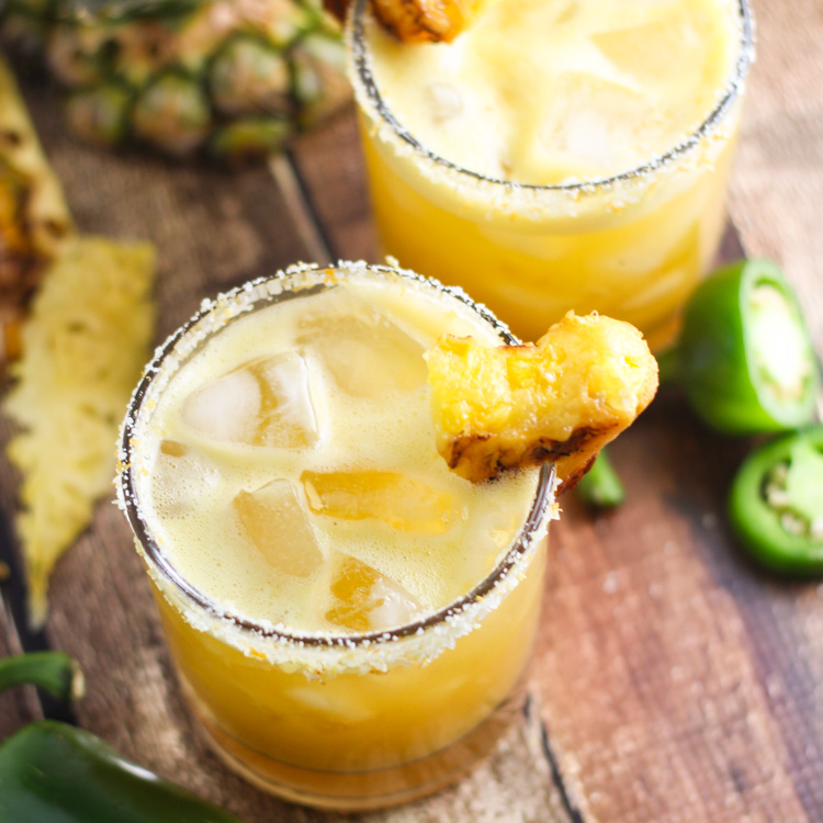 This Grilled Pineapple Jalapeno Margarita is the perfect blend of sweet, spicy, and smoky. Caramelized grilled pineapple combines with jalapeno infused tequila & a splash of vanilla. | platingsandpairings.com