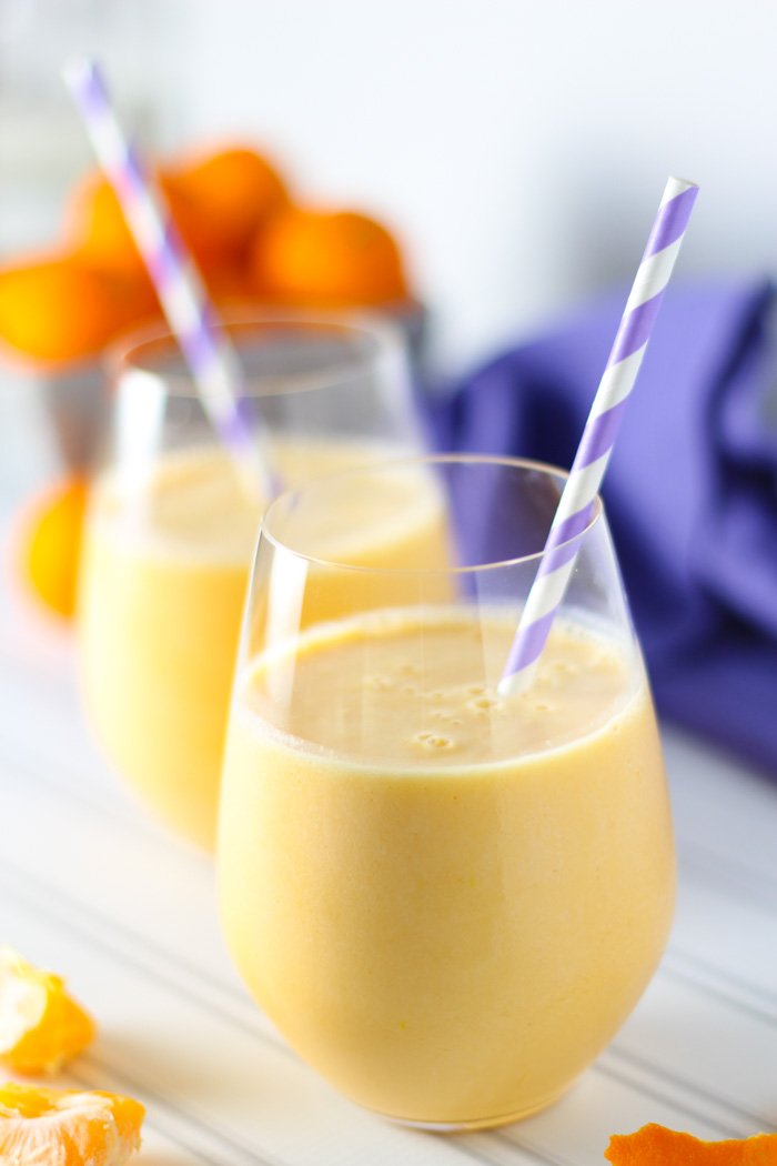 Two orange julius smoothies in glasses with purple striped straws.