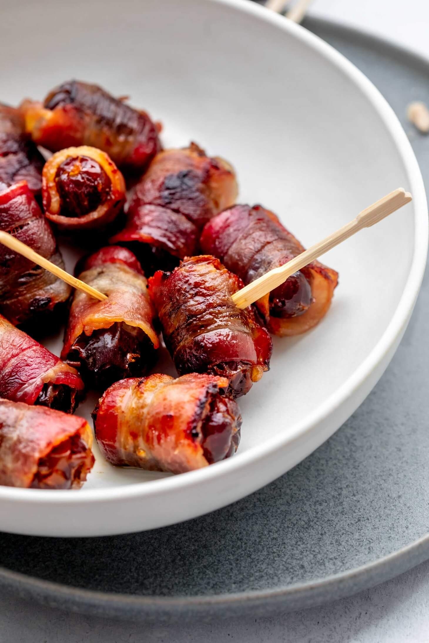 Side view of bowl of cooked bacon wrapped dates.