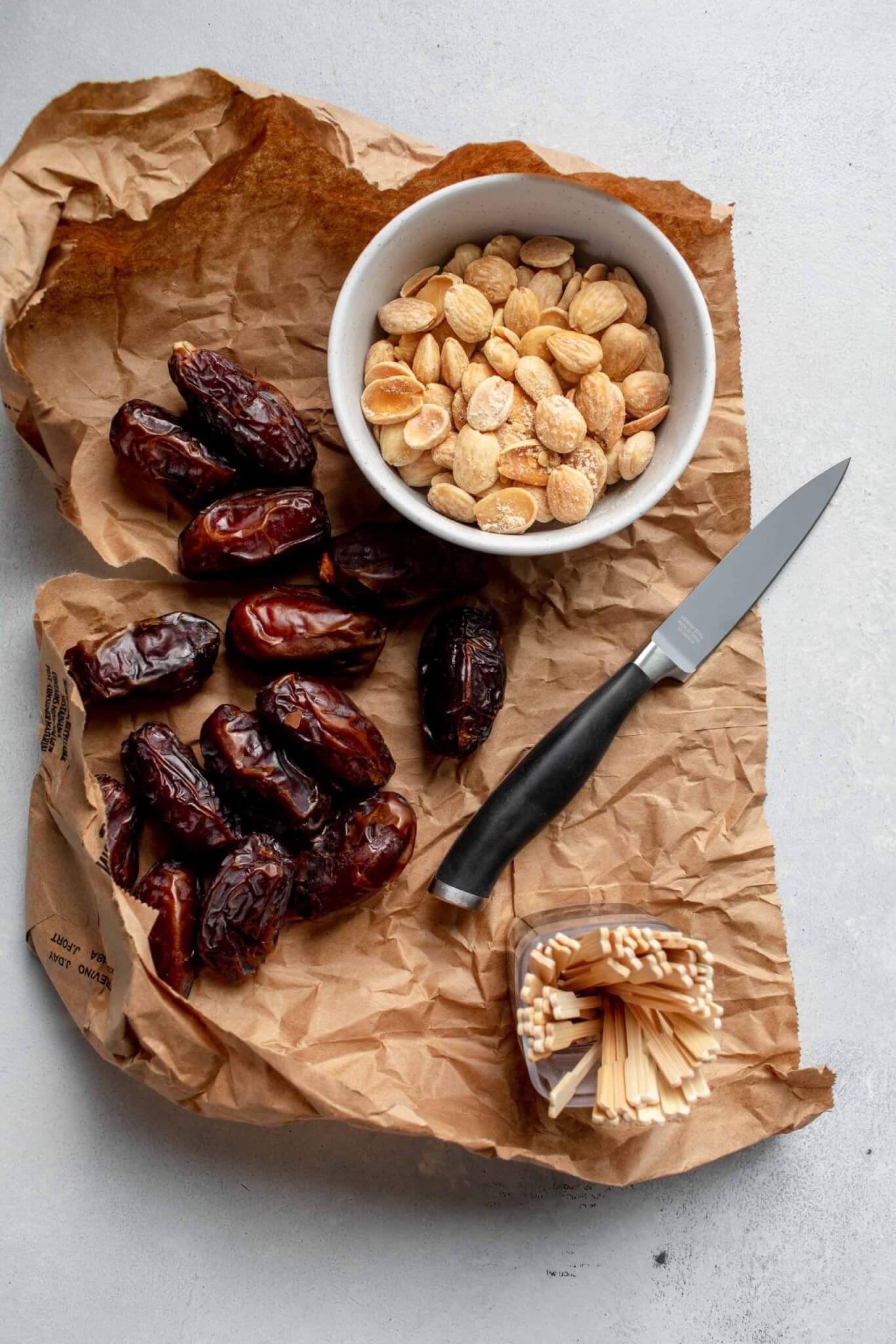 Dates on brown paper bag next to bowl of almonds.
