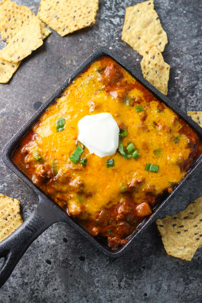 Take your snacking to the next level with this Cheesy Enchilada Dip. Beans are layered with ground beef and enchilada sauce, and topped with lots of melty cheese, green onions and a dollop of sour cream. | platingsandpairings.com