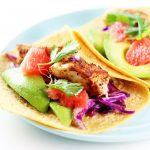 These Grapefruit & Avocado Fish Tacos are a delicious, healthy option for #TacoTuesday. Baked (not fried), and served with fresh grapefruit, creamy avocado, and a tangy cabbage slaw. | platingsandpairings.com