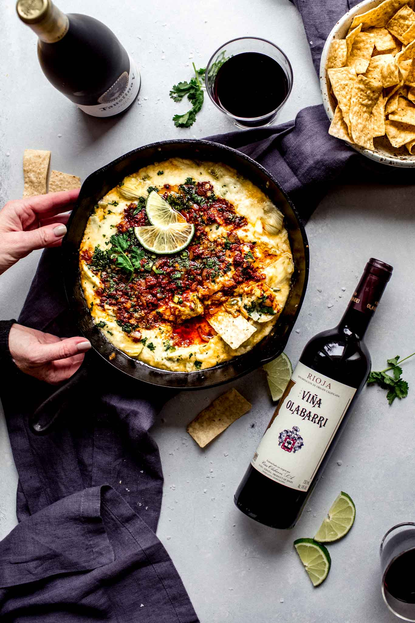 Hands holding skillet of queso blanco next to two bottles of wine.