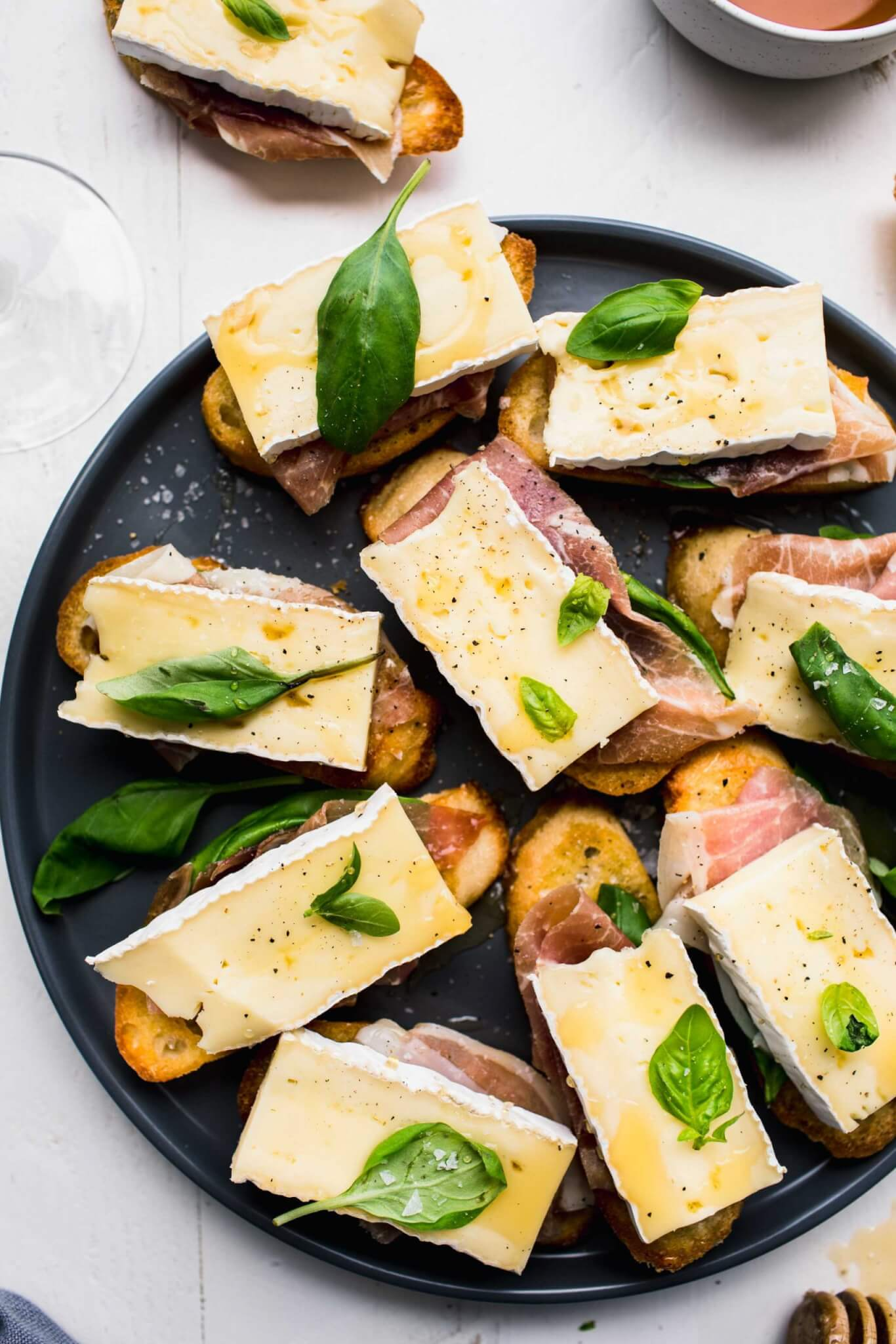 Crostini topped with brie, basil and prosciutto arranged on grey plate next to honey wand.