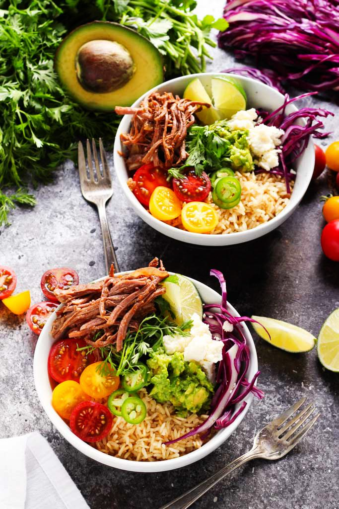 These Slow Cooker Steak Carnitas Bowls are super simple to make with the help of your crockpot. Finish them off with a quick guacamole and a combination of your favorite toppings for a healthy weeknight dinner | platingsandpairings.com