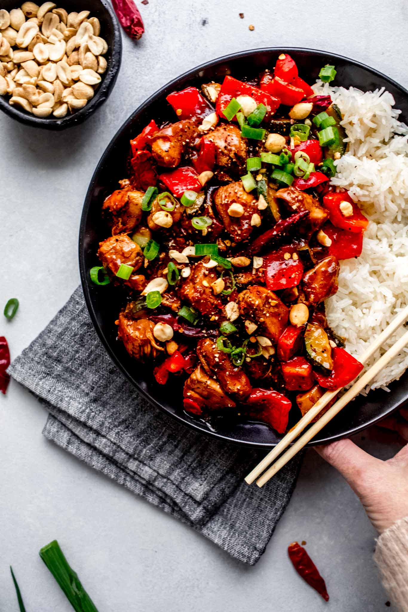 Hand holding plate of slow cooker kung pao chicken.