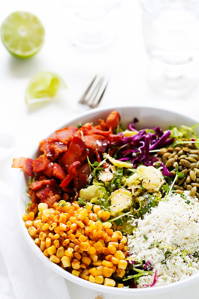 This Shaved Brussels Sprouts Salad with Cumin Lime Vinaigrette has a southwestern kick with cotija cheese, pepitas, roasted corn and bacon. | platingsandpairings.com