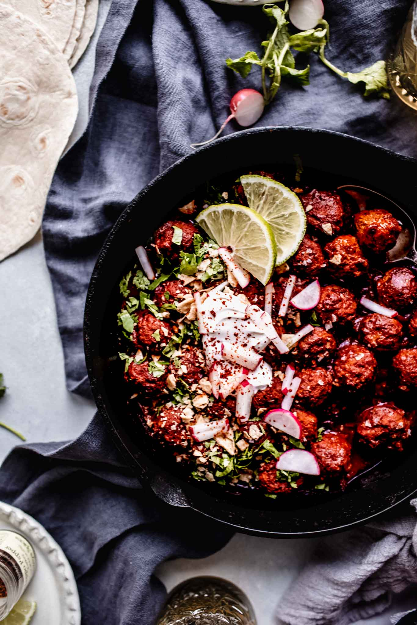Overhead shot of mexican meatballs in skillet topped with sour cream, limes and radishes.