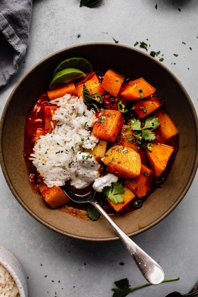 Overhead shot of potato vindaloo with rice and greek yogurt.