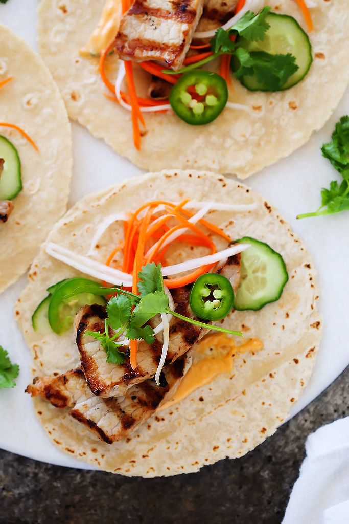 These Banh Mi Pork Tacos are perfect for grilling season and can be made in under 30 minutes! Tender grilled pork is topped with quick-pickled vegetables, hot chili mayo, jalapenos and cilantro. It's your favorite sandwich, in taco form!   platinigsandpairings.com