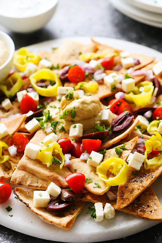 These Mediterranean Nachos with Hummus are topped with crumbly feta cheese, cherry tomatoes, pepperoncini, Kalamata olives and a tangy tzatziki sauce. They make a perfect party appetizer!   platingsandpairings.com
