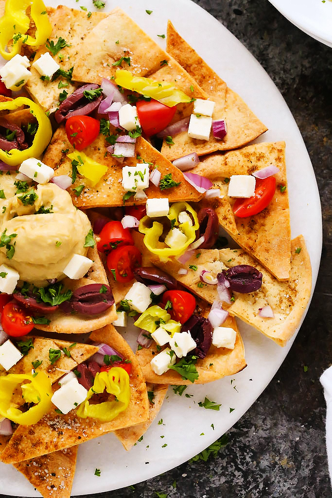 These Mediterranean Nachos with Hummus are topped with crumbly feta cheese, cherry tomatoes, pepperoncini, Kalamata olives and a tangy tzatziki sauce. They make a perfect party appetizer! | platingsandpairings.com
