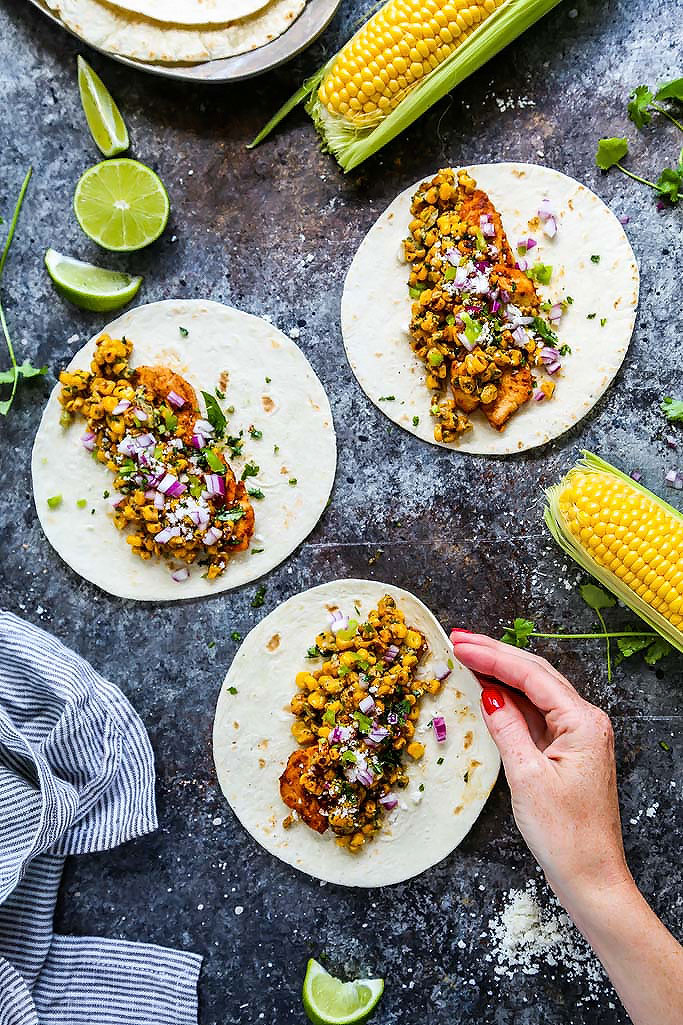 These Mexican Street Corn Chicken Tacos put a fun twist on elotes or grilled Mexican corn on the cob that's slathered in a tangy cream sauce and sprinkled with chili powder. Plus, they come together in just 20 minutes! | platingsandpairings.com