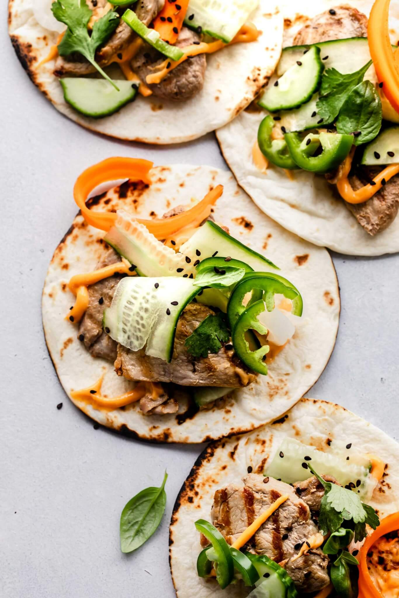 Four banh mi tacos arranged on grey slate countertop.