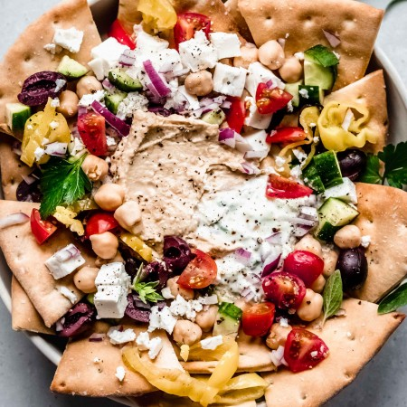 Overhead shot of greek nachos arranged on plate with toppings.