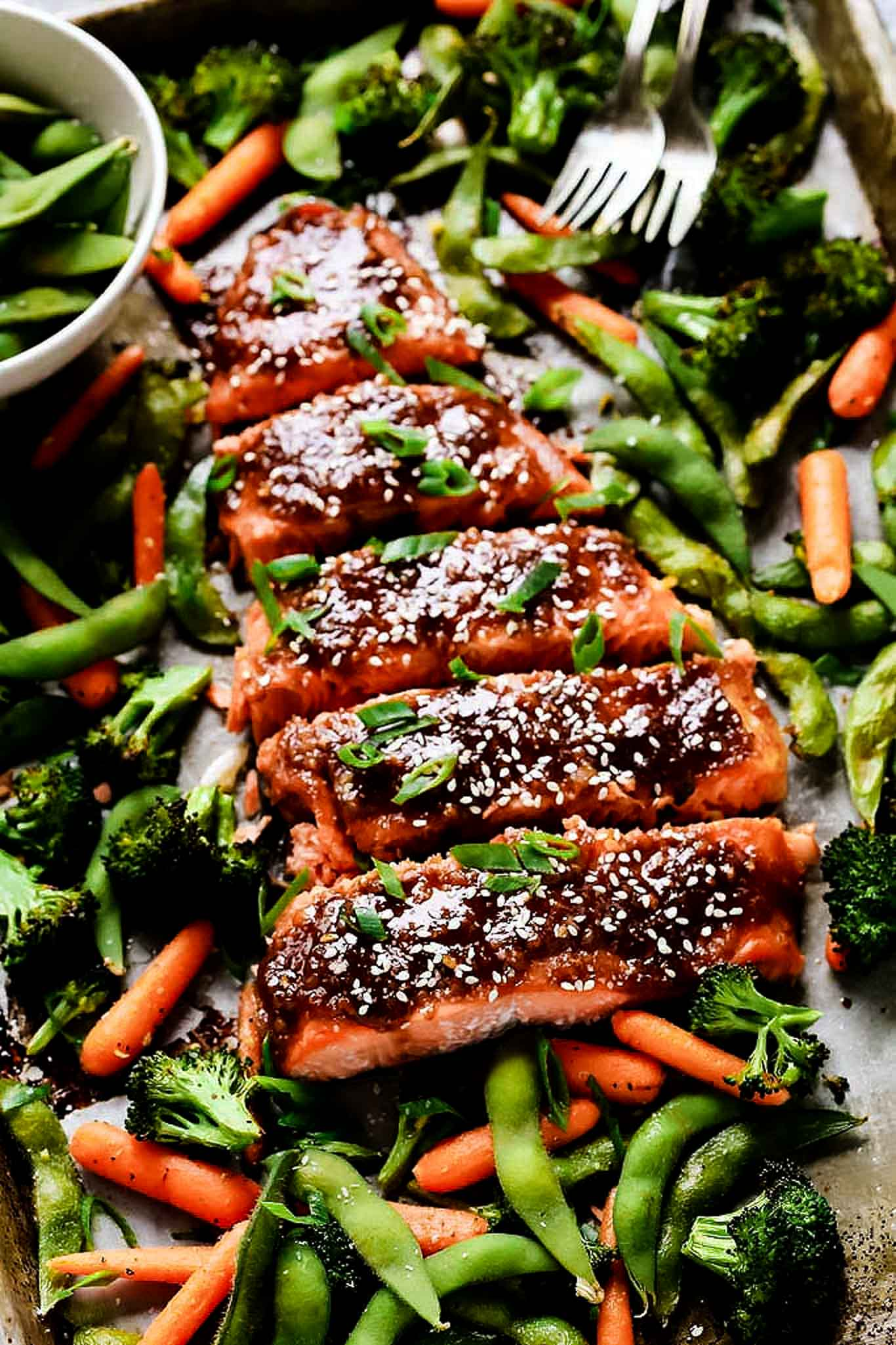 Side view of miso salmon on sheet pan with veggies.