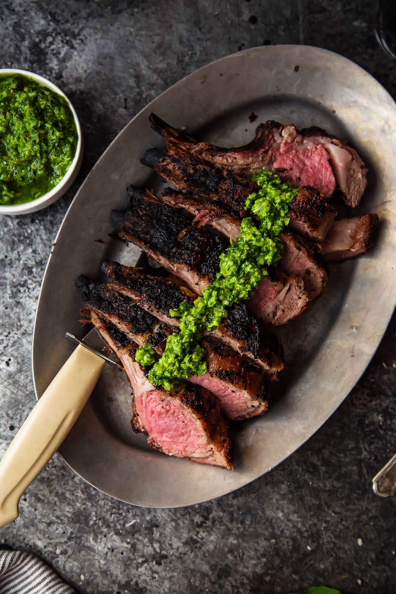 Grilled Rack of Lamb with Pistachio Basil Pesto will upgrade your next BBQ or tailgate. Frenched rack of lamb is grilled, sliced & topped with basil pesto. | platingsandpairings.com