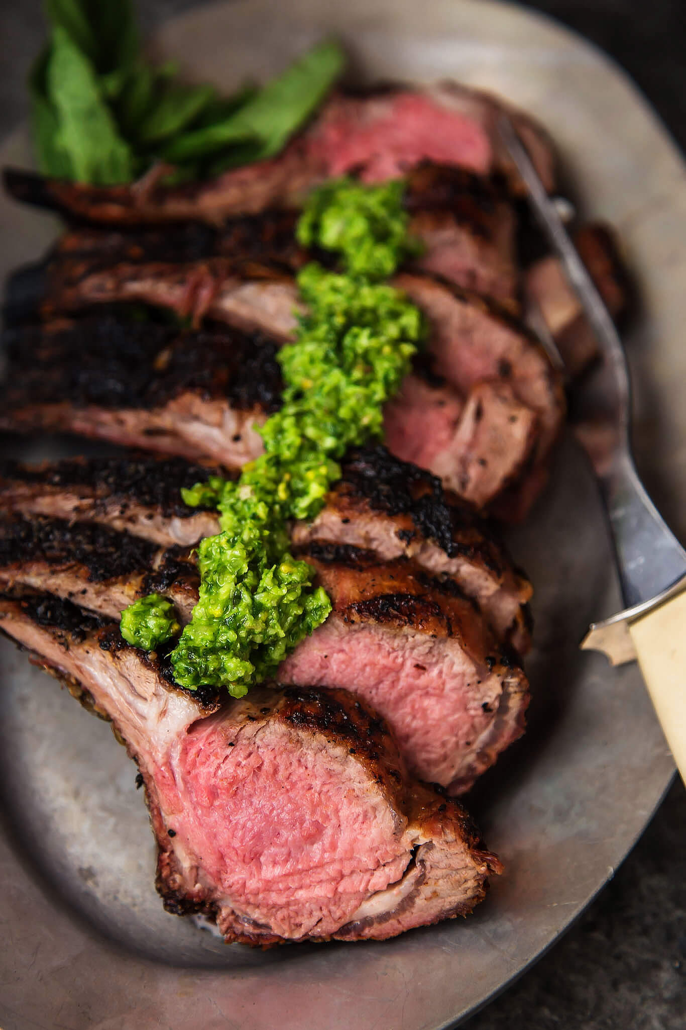 Grilled Rack of Lamb with Pistachio Basil Pesto will upgrade your next BBQ or tailgate. Frenched rack of lamb is grilled, sliced & topped with basil pesto. | platingsandpairings.com