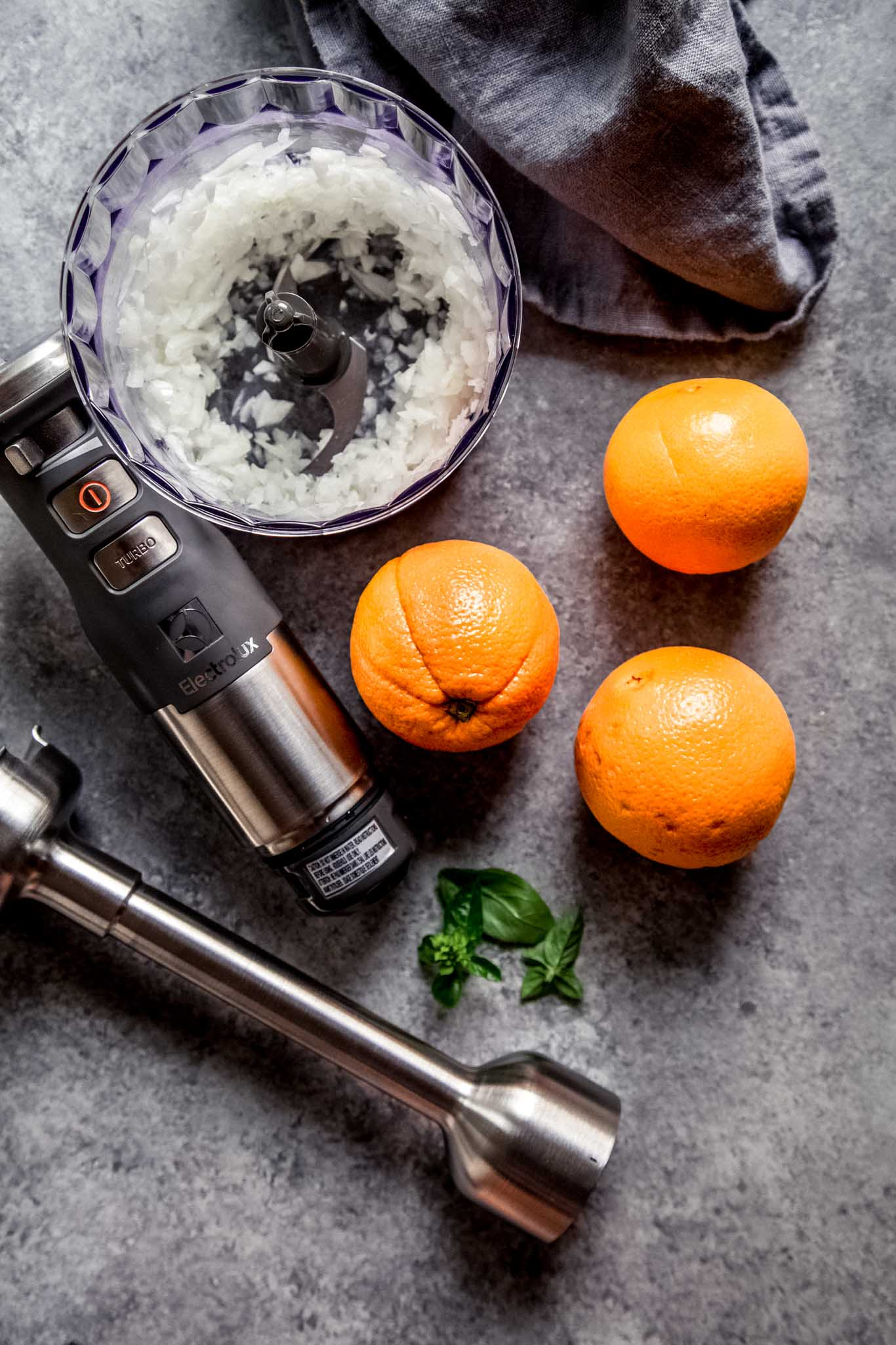 Oranges and onions next to immersion blender.