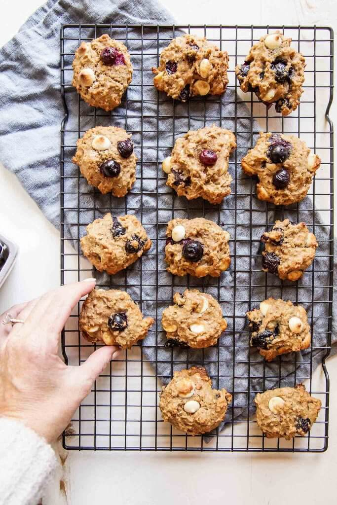 Hand reaching for quinoa breakfast cookie.