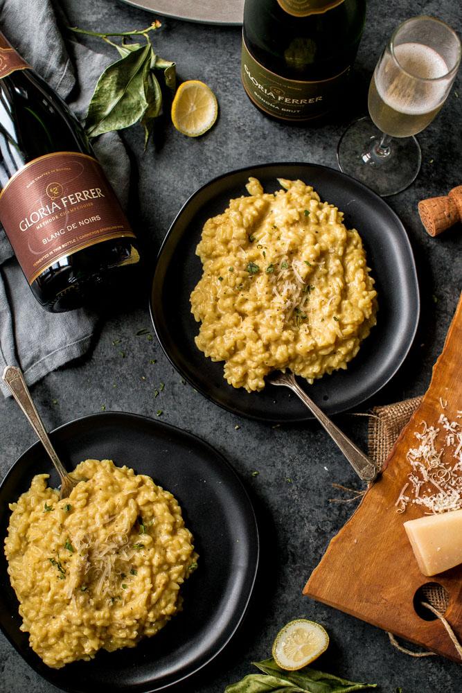 Two bowls of Lemon Mascarpone Risotto with sparkling wine alongside.