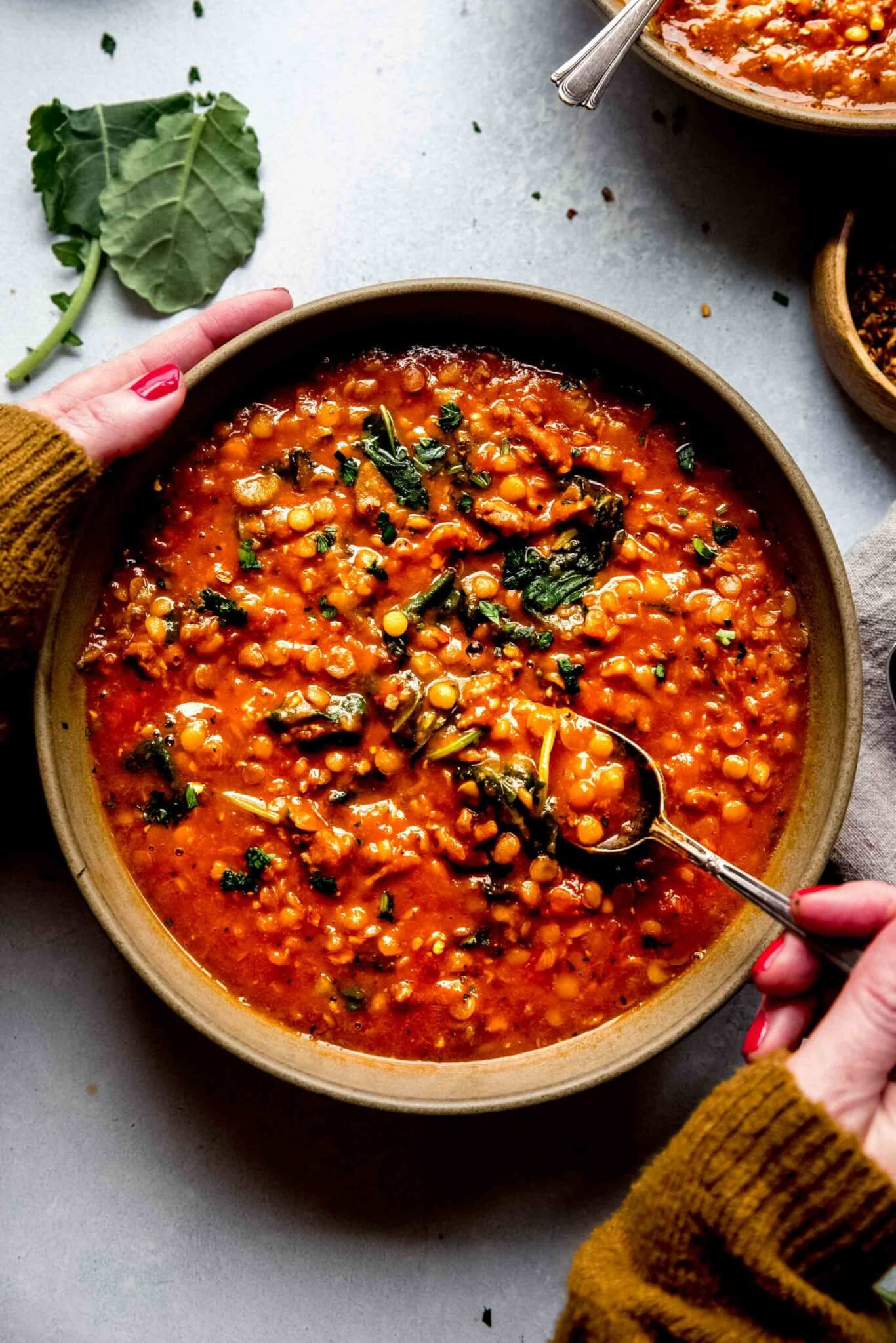 Hands holding bowl of instant pot lentil soup.