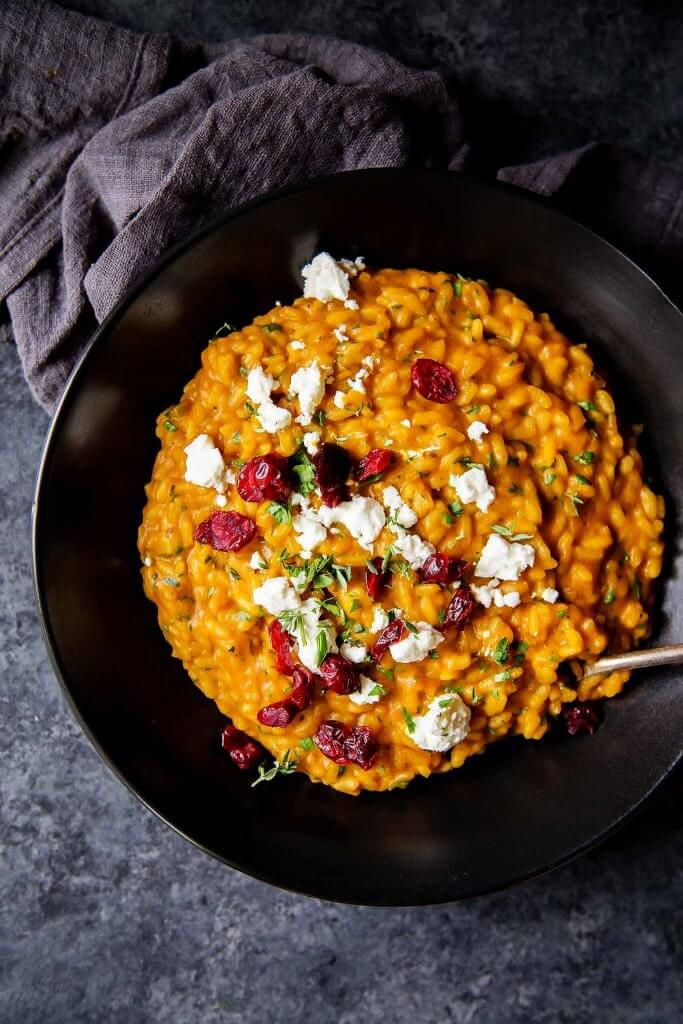 Pumpkin Risotto with Goat Cheese and Dried Cranberries in bowl - Close up shot.