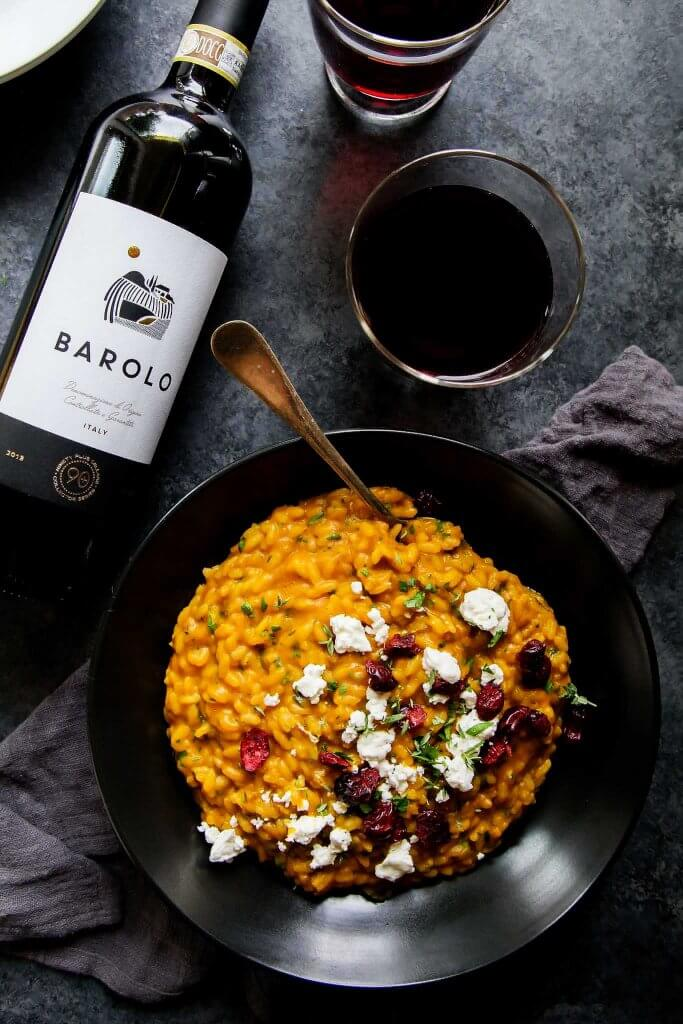 Pumpkin Risotto with Goat Cheese and Dried Cranberries in bowl with a Barolo wine pairing.