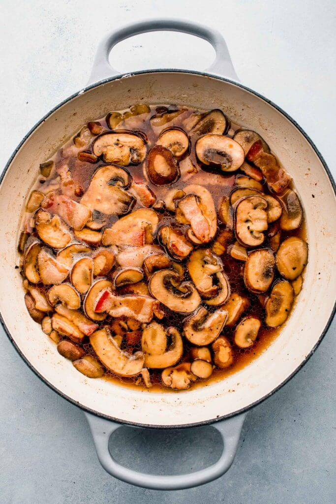 Chicken in skillet with marsala wine, mushrooms and bacon.