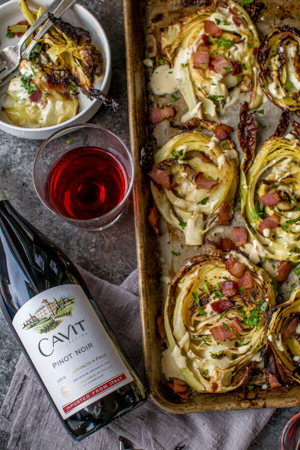 Roasted Cabbage Steaks topped with bacon & garlicky creme fraiche. next to bottle of Pinot Noir.