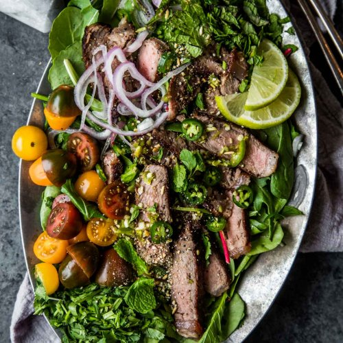 Thai beef salad overhead shot with toasted rice powder on the side.