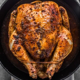 Overhead shot of roasted chicken in cast iron skillet.