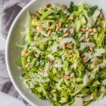 Bowl of shaved fennel and celery salad topped with toasted pine nuts and parmesan