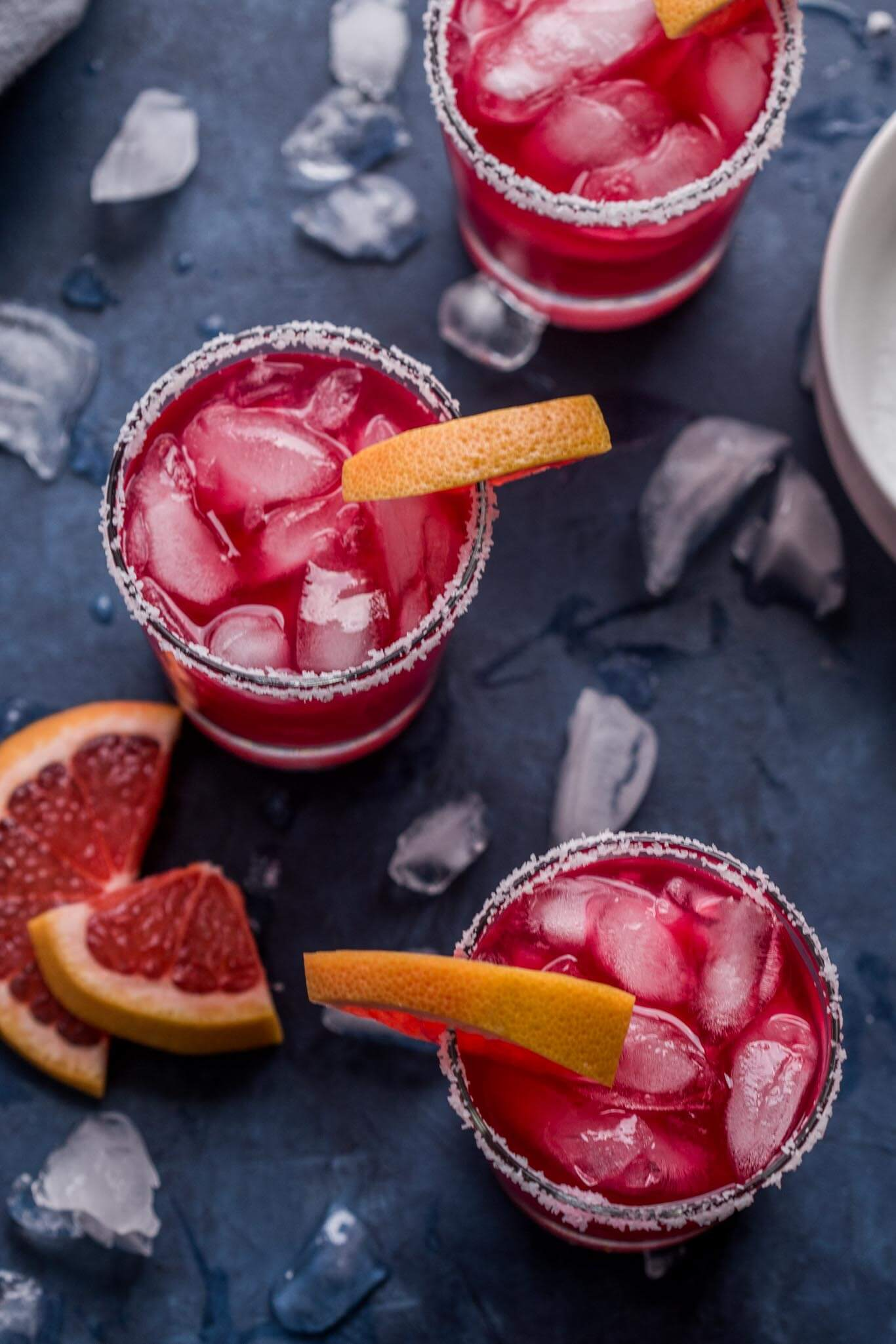 Three hibiscus tea margaritas with ice on a dark blue background.