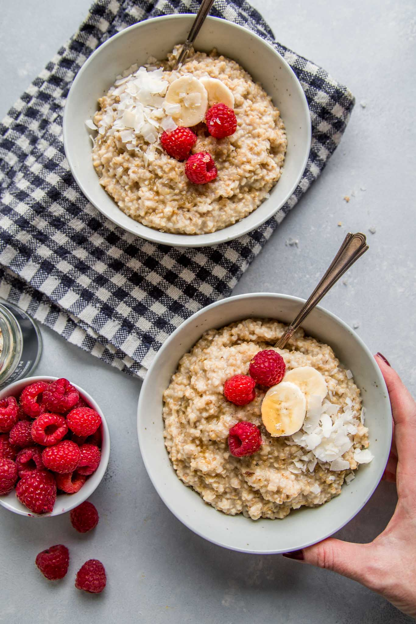 Two bowls of Instant Pot Steel Cut Oatmeal with hand reaching for them.