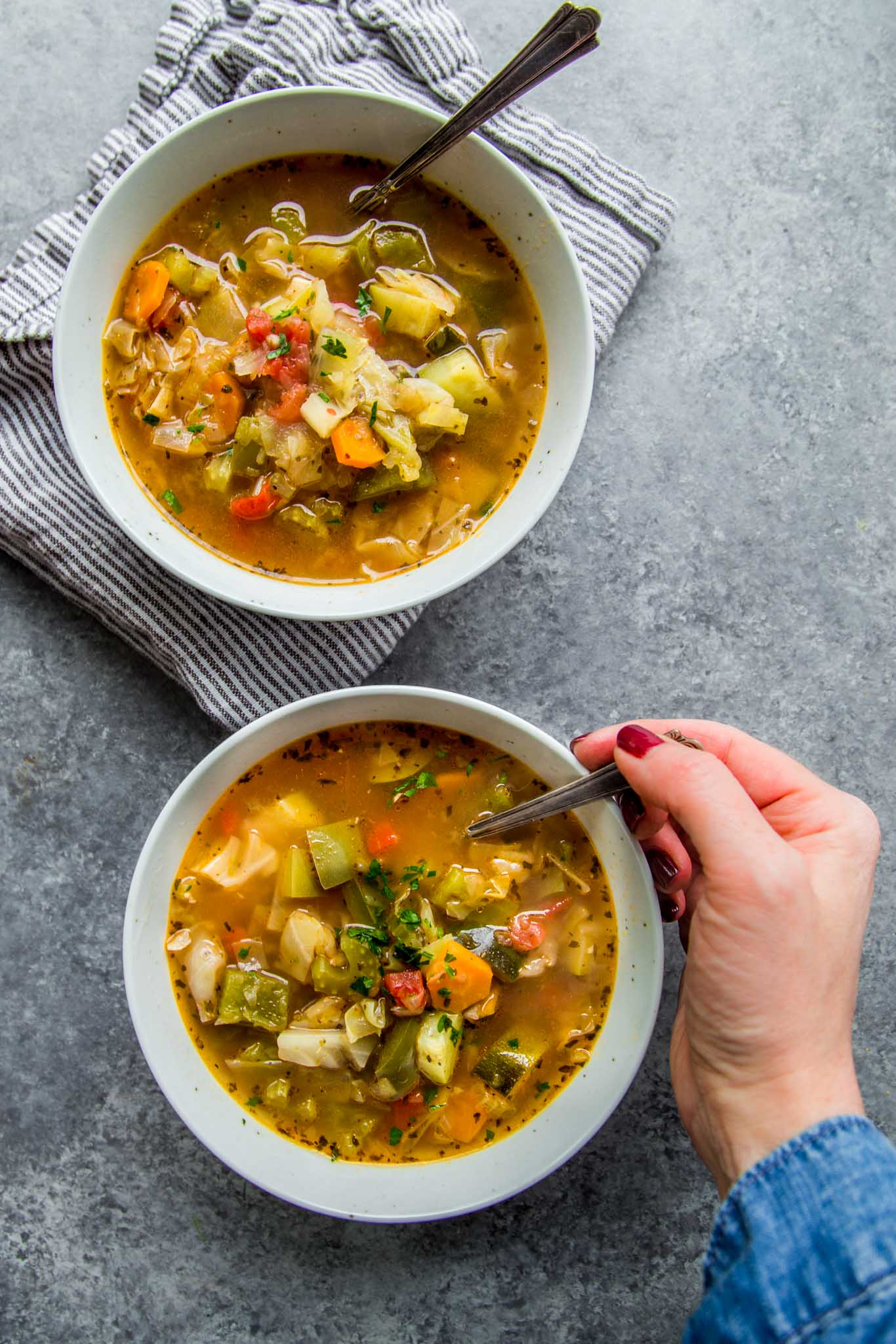 Two bowls of instant pot weight loss soup with hand eating.