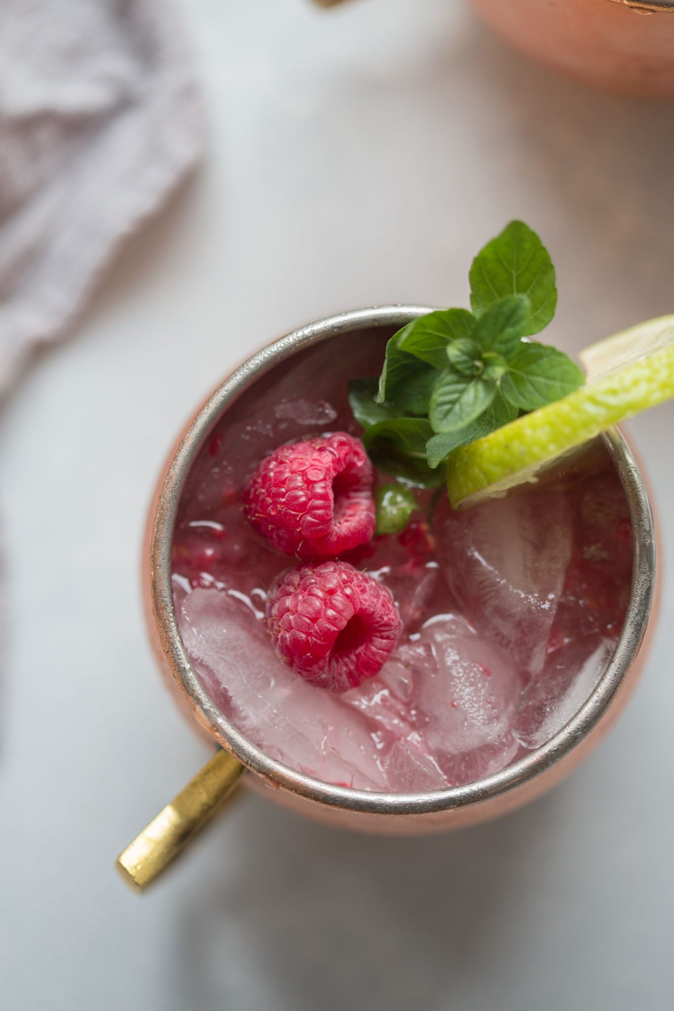 Close up mug of Raspberry Lime Moscow Mule garnished with raspberries, mint and lime in a copper mug.