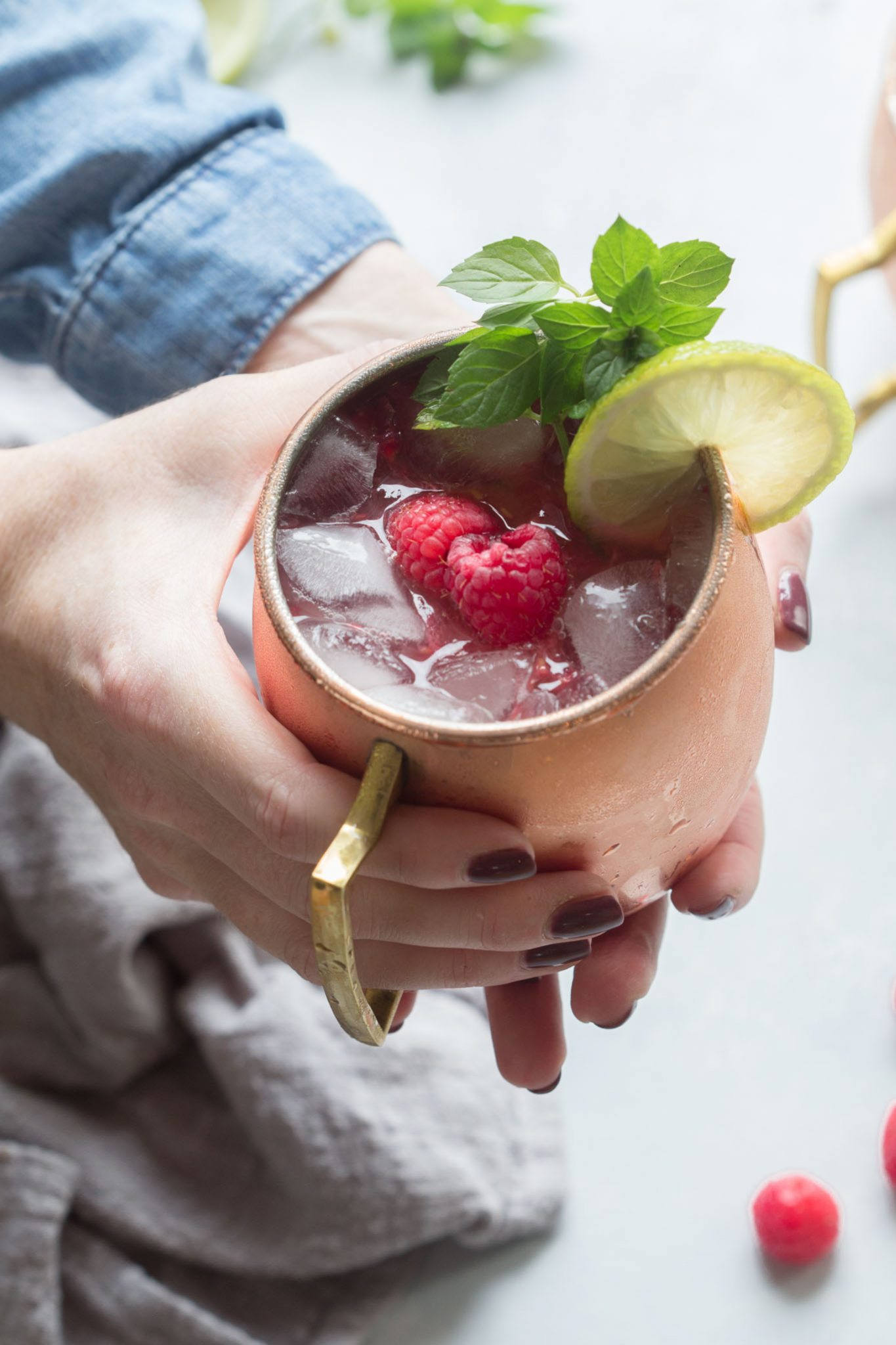 Close up of hands holding Raspberry Moscow Mule with mint leaves, lime wheel and raspberries.