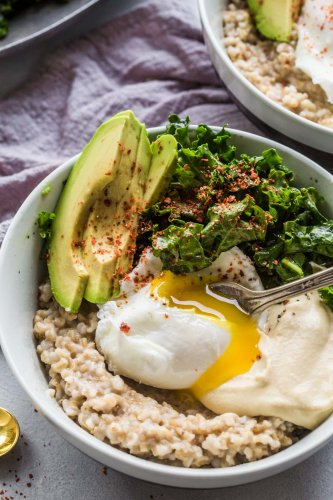 Avocado & Kale Savory Oat Bowls are the perfect way to start your day. Hearty oatmeal is topped with avocado, lemony kale salad, hummus and aleppo pepper for a protein-packed breakfast.