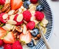 Overhead close up of bowl of oatmeal topped with berries and almonds.
