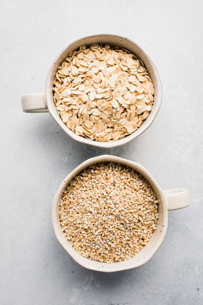 Two bowls of oatmeal, one with steel cut oats and the other with regular oats.